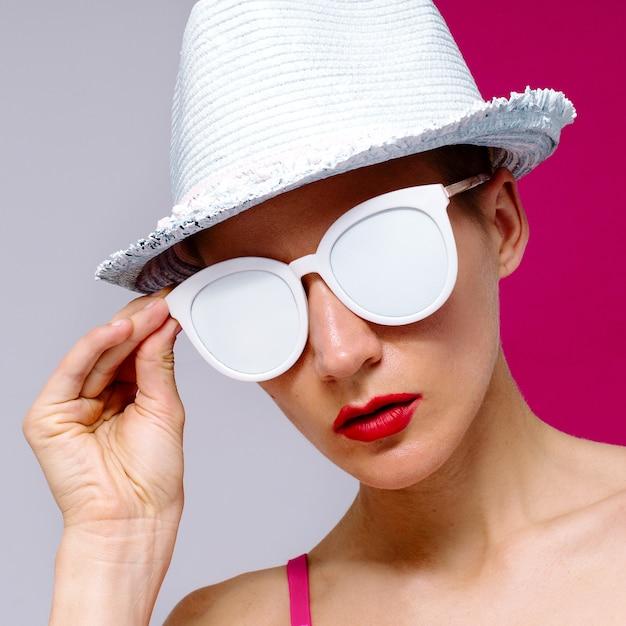 Modello stile pop art in occhiali da sole e un cappello. beach minimal Foto Premium