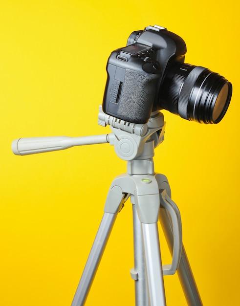 Moderna fotocamera digitale con un treppiede su un tavolo giallo Foto Premium