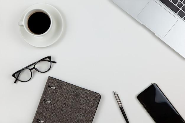 Moderno spazio di lavoro unisex, vista dall'alto. blocco note, penna, caffè, smartphone, occhiali, computer portatile su sfondo bianco, copia spazio, piatto laici Foto Premium