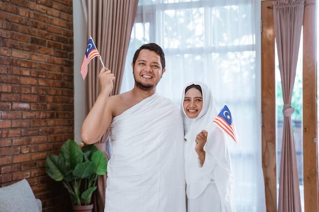 Moglie e marito asiatici che tengono bandiera nazionale della malesia Foto Premium