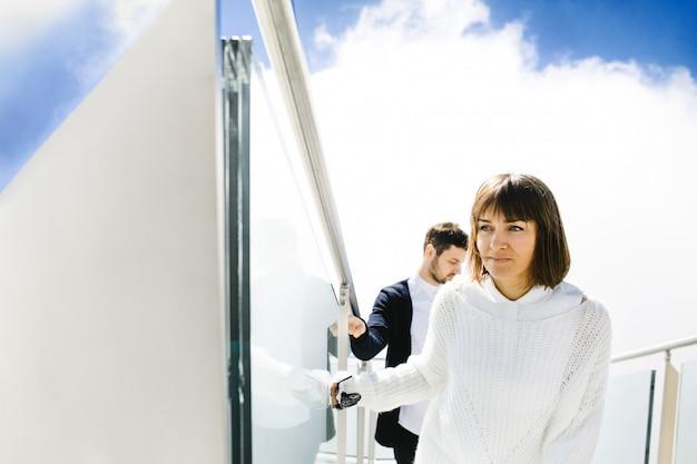 Moglie e marito salendo sulle scale in cielo Foto Gratuite