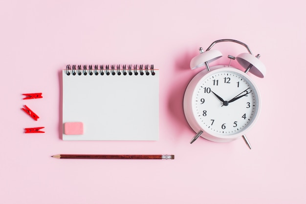 Molletta rossa; blocco note a spirale; gomma da cancellare; matita e sveglia su sfondo rosa Foto Gratuite