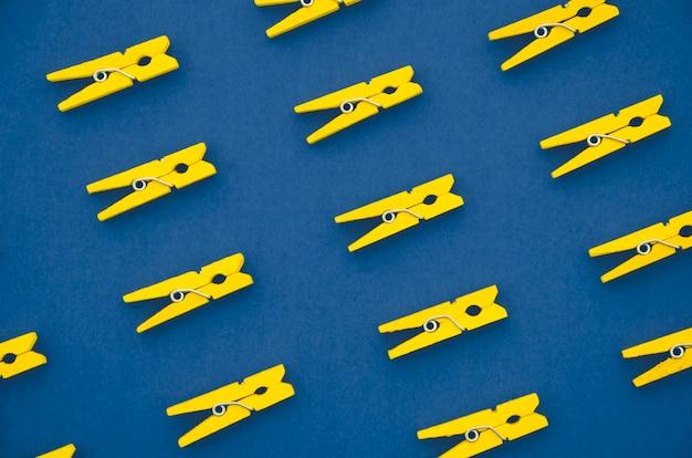 Mollette per abiti gialle su fondo blu Foto Gratuite