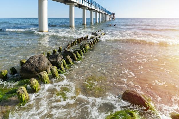 Molo sulla costa. surf onde con schiuma di mare e alghe sulla spiaggia turistica. bellissima costa alla luce del sole. vista sul mare di giorno. Foto Premium
