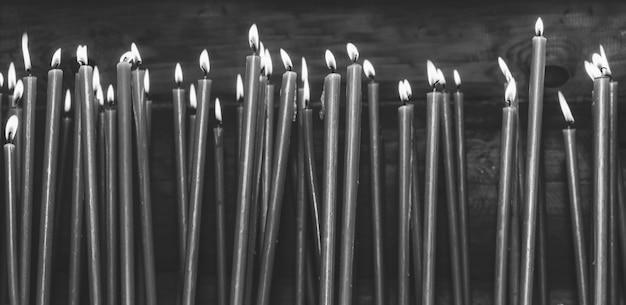 Molte candele brucianti della cera nel tempio, foto in bianco e nero Foto Premium