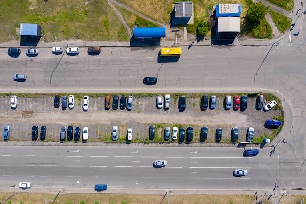 Molte macchine sono parcheggiate in un parcheggio intercettante spontaneo tra due viali alla periferia della città. Foto Premium