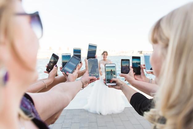 Molte mani femminili con i telefoni intelligenti che fanno le foto Foto Premium