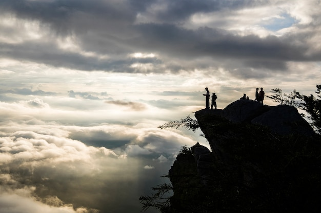 Molte nuvole sull'alba con persone silhouette in cima alla montagna Foto Gratuite