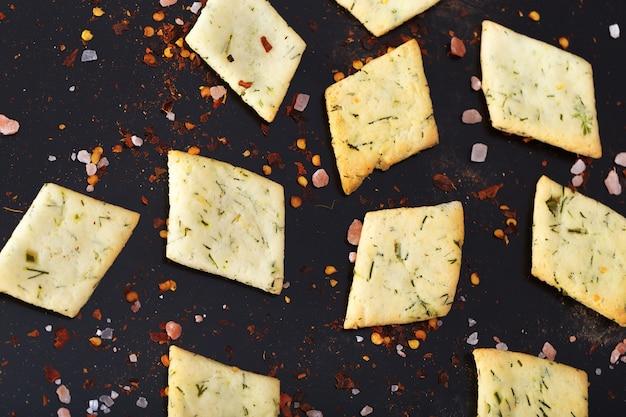 Molte patatine si trovano in modo irregolare su un tavolo nero. Foto Premium
