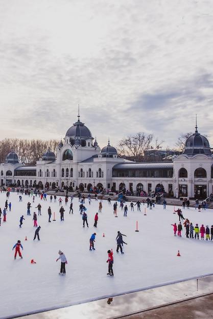 Molte persone trascorrono le loro vacanze pattinando nella pista di pattinaggio di park city a budapest, in ungheria Foto Premium
