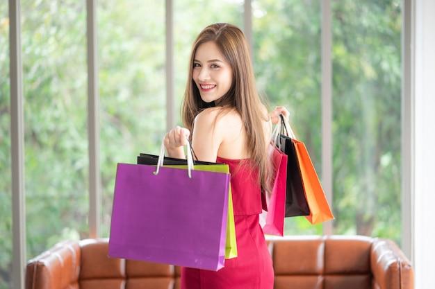 Molte ragazze sono amanti dello shopping come lei. è bellissima con un vestito rosso e tiene gli acquisti b Foto Premium