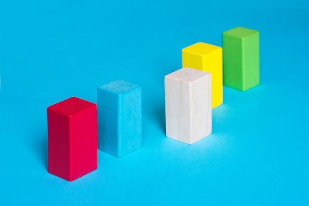 Molti blocchi colorati in una riga e un blocco di legno su sfondo blu Foto Premium