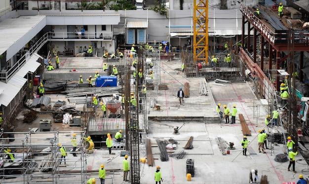 Molti lavoratori in cantiere ed attrezzature per l'edilizia Foto Premium