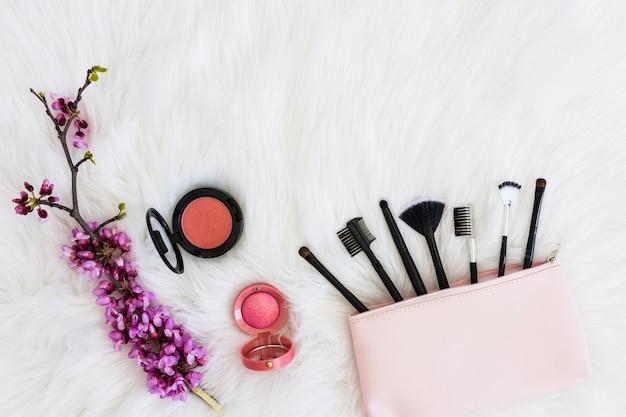 Molti pennelli per il trucco dalla borsa rosa; ramoscello fiore e cipria compatta su soffice pelliccia bianca Foto Gratuite