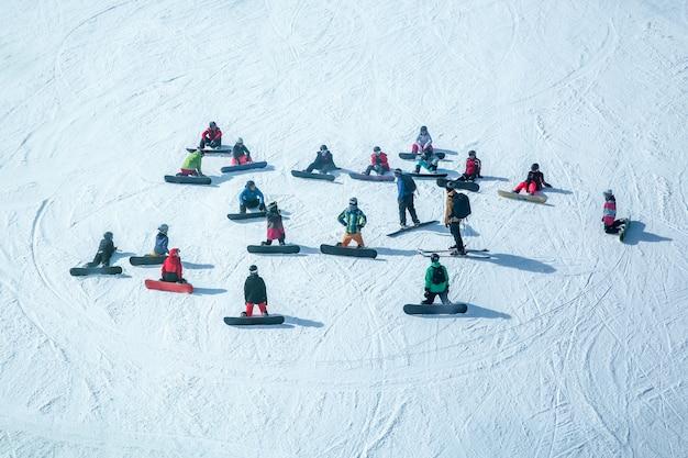 Molti sciatori e snowboarder si riposano su una pista nel comprensorio sciistico Foto Premium