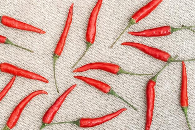 Molto piccolo primo piano caldo dei peperoncini rossi in ordine casuale sul tessuto naturale della tela di sacco Foto Premium