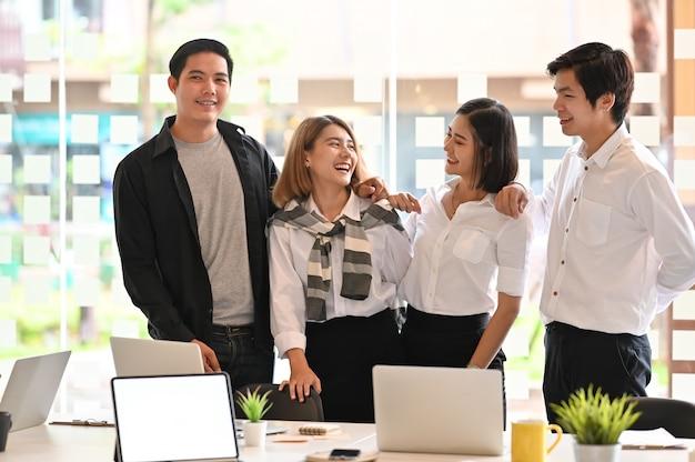 Momento felice dei giovani colleghi di affari nella stanza dell'ufficio. Foto Premium