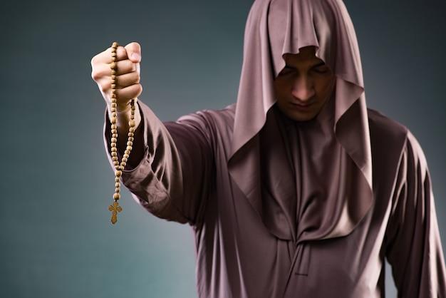 Monaco nel concetto religioso su sfondo grigio Foto Premium