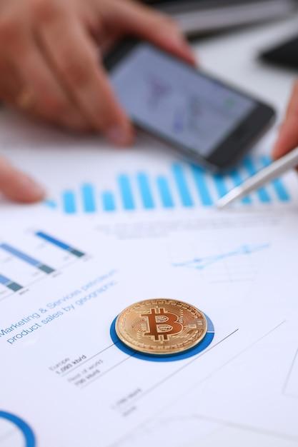 Moneta dorata del segno di btc che si trova al primo piano del grafico di statistiche. Foto Premium