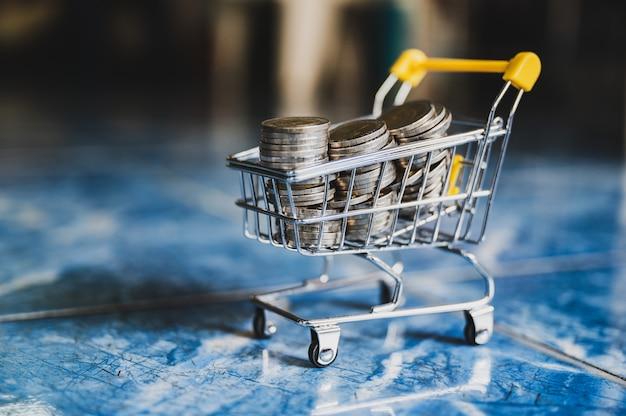 Monete dei soldi nel fondo astratto della sfuocatura del carrello di acquisto giallo. Foto Premium