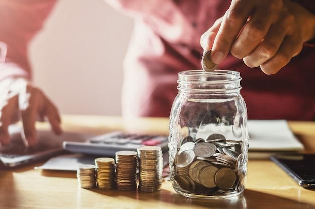 Monete della tenuta dell'uomo d'affari che mettono in vetro. concetto di risparmio di denaro e contabilità finanziaria Foto Premium