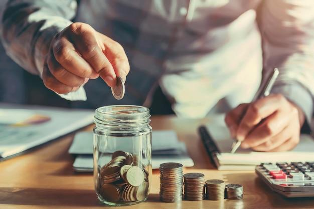 Monete della tenuta della donna di affari e mettere in vetro Foto Premium