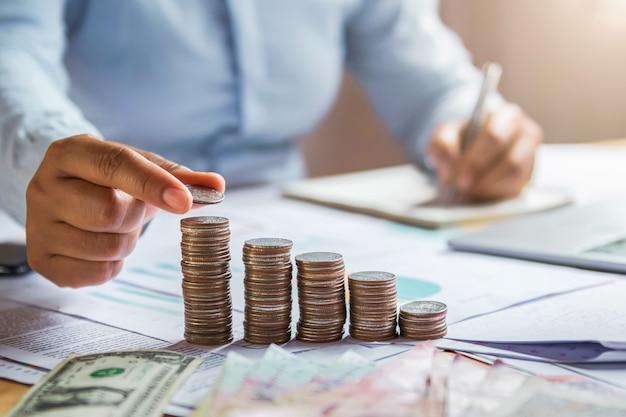 Monete della tenuta della mano della donna di affari da impilarsi sulla finanza dei soldi di risparmio di concetto di scrittorio Foto Premium