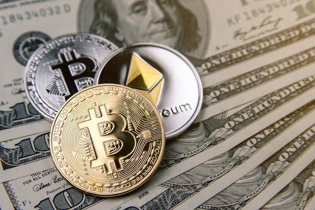 Monete di criptovaluta di oro, argento bitcoin ed ethereum su banconote da cento dollari. investimento di denaro virtuale. concetto di affari di criptovaluta. Foto Premium