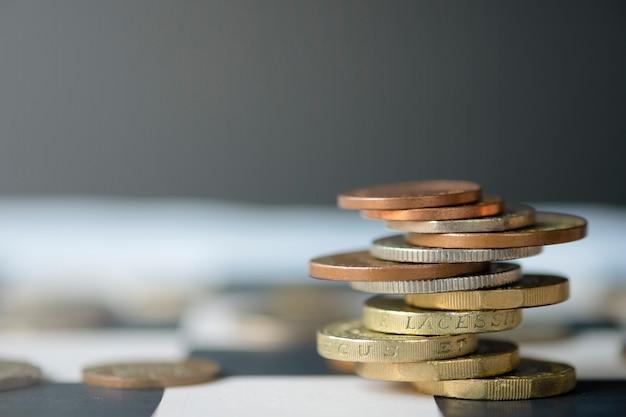 Monete di sterlina che impilano sulla tabella di scacchi con priorità bassa nera Foto Premium