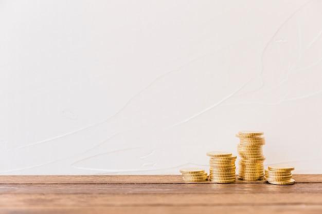 Monete dorate impilate davanti al muro Foto Gratuite