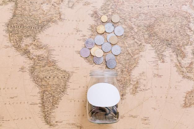 Monete e un vaso aperto sulla mappa del mondo Foto Gratuite