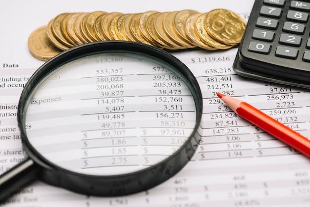 Monete; lente d'ingrandimento; matita e calcolatrice sul rapporto finanziario Foto Gratuite