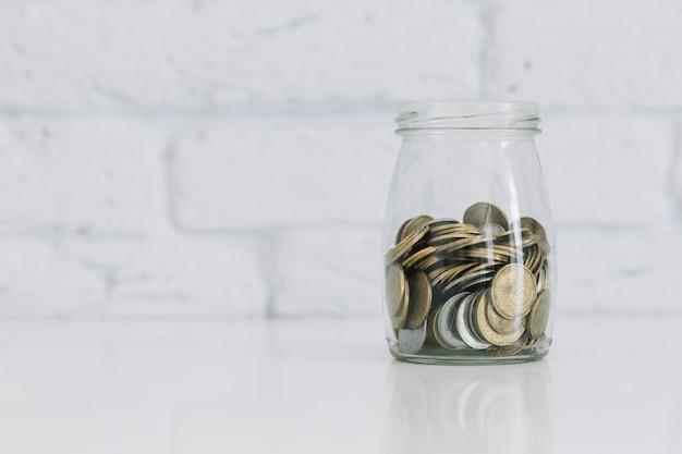Monete nel vaso di vetro sulla scrivania contro il muro bianco Foto Gratuite