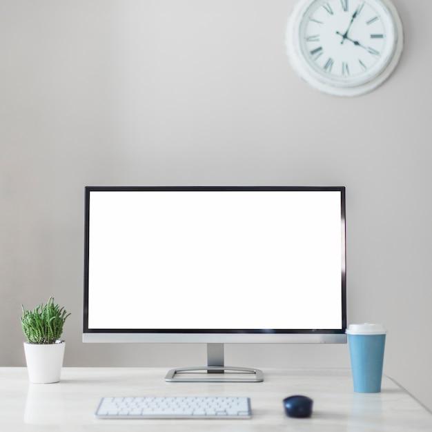 Monitora vicino a tazza, pianta e tastiera Foto Gratuite