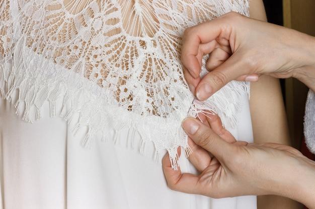 Montaggio abito da sposa. sarta prepara il vestito per il montaggio Foto Premium