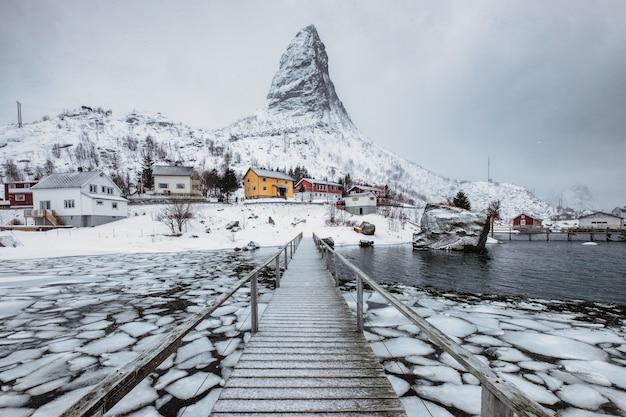 Montagna della neve con il villaggio scandinavo sulla linea costiera con il ponte di legno alle isole di lofoten Foto Premium