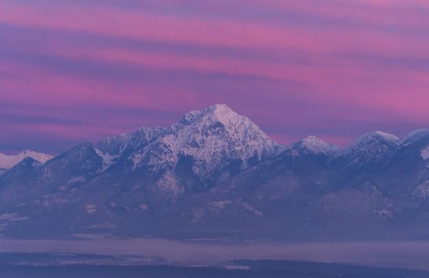 Montagna di pietra grigia coperta da neve Foto Gratuite