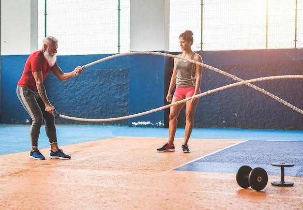 Montare l'uomo con la corda di battaglia in palestra funzionale di allenamento funzionale - personal trainer che motiva l'atleta maschio all'interno del centro del club benessere - concetto di tendenze di allenamento e sport - concentrarsi sul corpo dell'uomo Foto Premium
