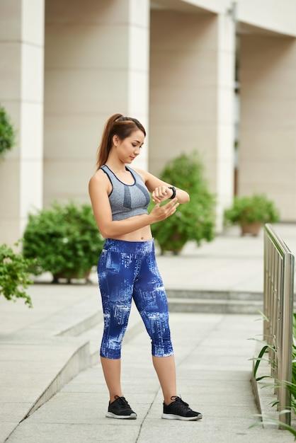 Montare la donna asiatica in cima e leggings in piedi in strada e guardando l'orologio sportivo Foto Gratuite