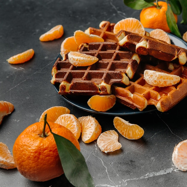 Morbidi waffle viennesi su un piatto con mandarini Foto Premium