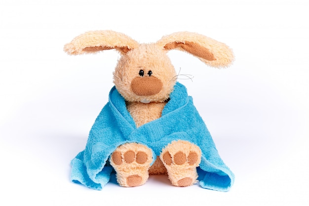 Morbido coniglietto di pezza in un asciugamano blu su uno sfondo bianco. Foto Premium