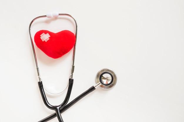 Morbido cuore rosso con stetoscopio su sfondo bianco Foto Gratuite