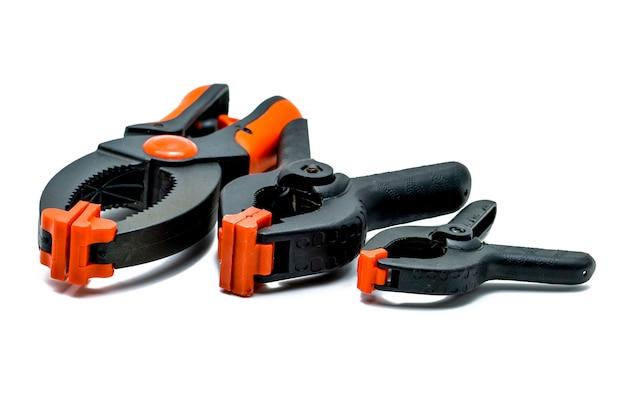 Morsetto a molla nero ed arancio isolato su fondo bianco. set di morsetti di plastica di piccole, medie e grandi dimensioni. strumenti di serraggio per lavori di carpenteria. utensili a mano per artigianato. attrezzatura di serraggio. Foto Premium