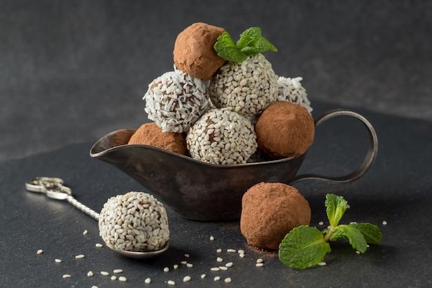 Morsi di energia con cacao in polvere, semi di sesamo e scaglie di cocco in salsiera sul tavolo grigio Foto Premium