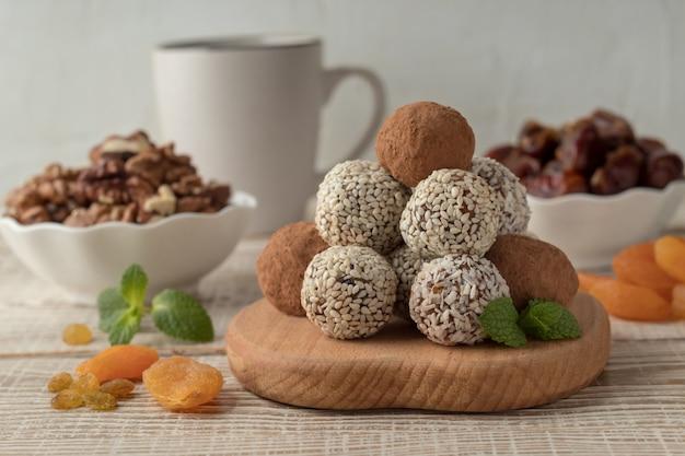 Morsi di energia con cacao in polvere, semi di sesamo e scaglie di cocco sul tavolo di legno bianco Foto Premium