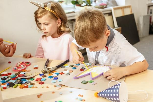Mosaico puzzle art per bambini, gioco creativo per bambini. due sorelle giocano a mosaico Foto Gratuite