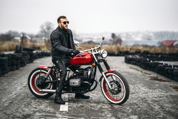 Moto rossa con pilota. l'uomo con una giacca di pelle nera e pantaloni sta lateralmente in mezzo alla strada. Foto Premium