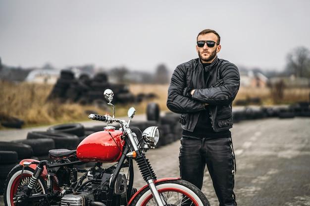 Moto rossa con pilota. un uomo con una giacca di pelle nera e pantaloni è in piedi vicino a una motocicletta con le mani giunte, sulla strada. i pneumatici sono posati sullo sfondo Foto Premium