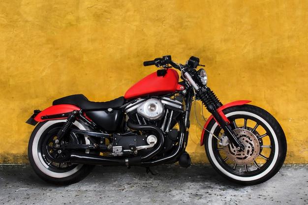 Moto rossa contro un muro giallo Foto Premium