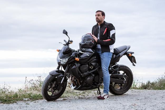 Motociclista del giovane con la sua motocicletta nera pronta a guidare, di fronte al mare Foto Premium